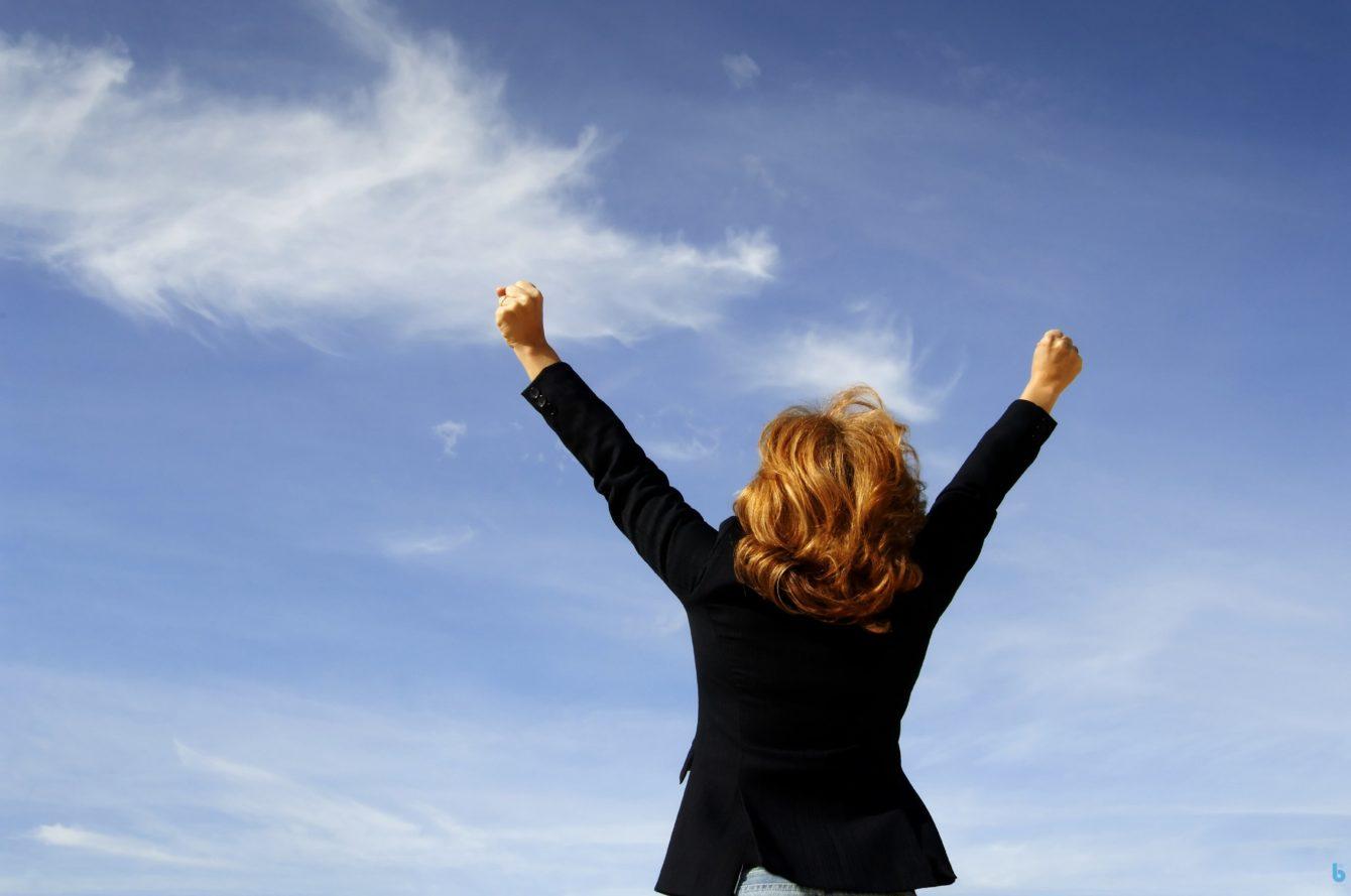 Kvinna med armarna i luften firar framgång i karriären